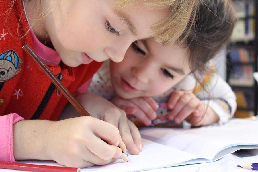 A photo of two children working together on homework -- teamwork