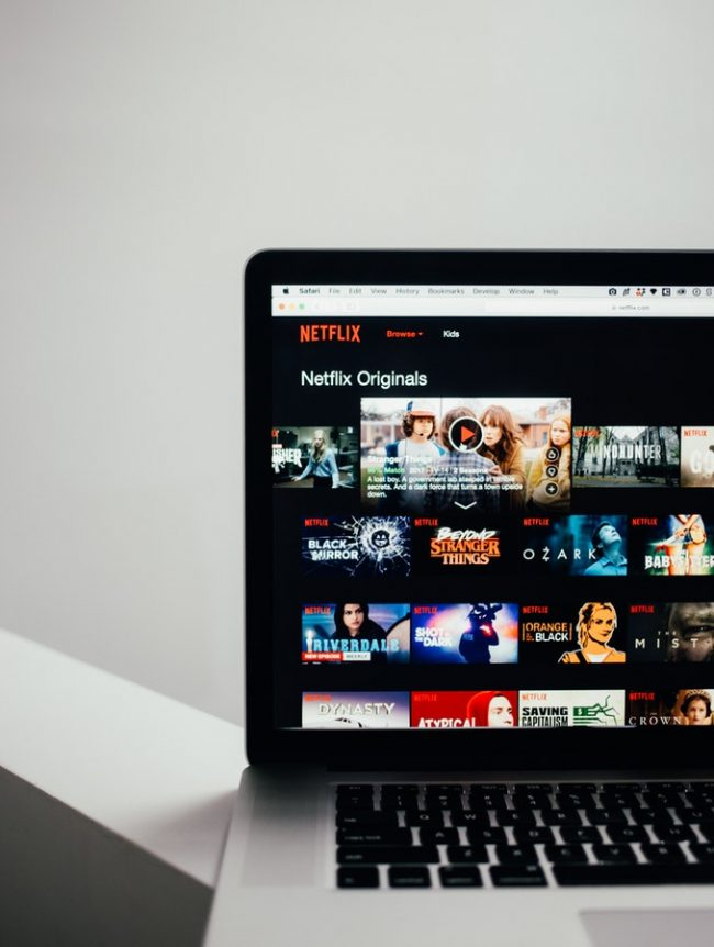 Photo of a laptop screen featuring Netflix TV shows and movies