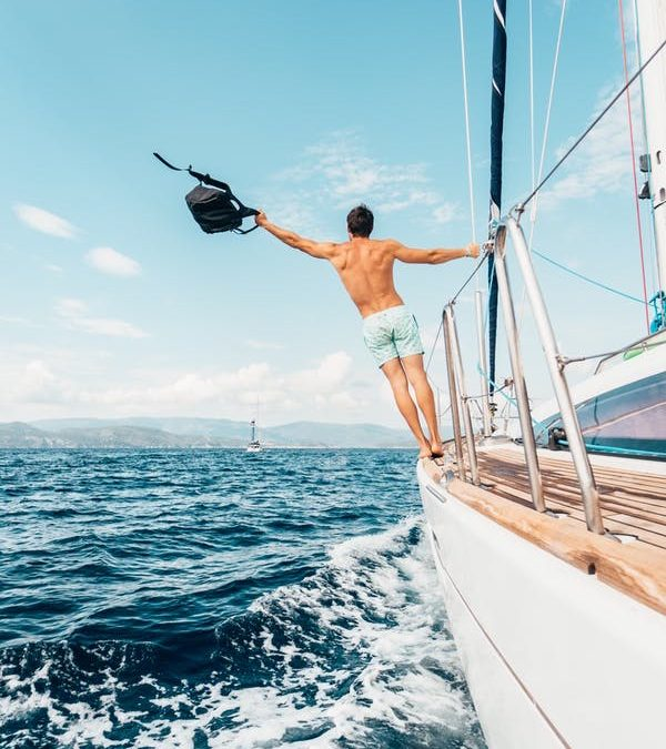 A photo of a man in swim trunks standing on the edge of a boat out at sea, arm outstretched, holding a backpack.