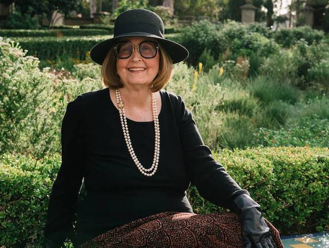 Photo of author Joan K. Lacy wearing a black shirt, black hat, black gloves, glasses and a pearl necklace.