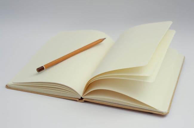 Character development tips: A picture of an open book with a pencil.